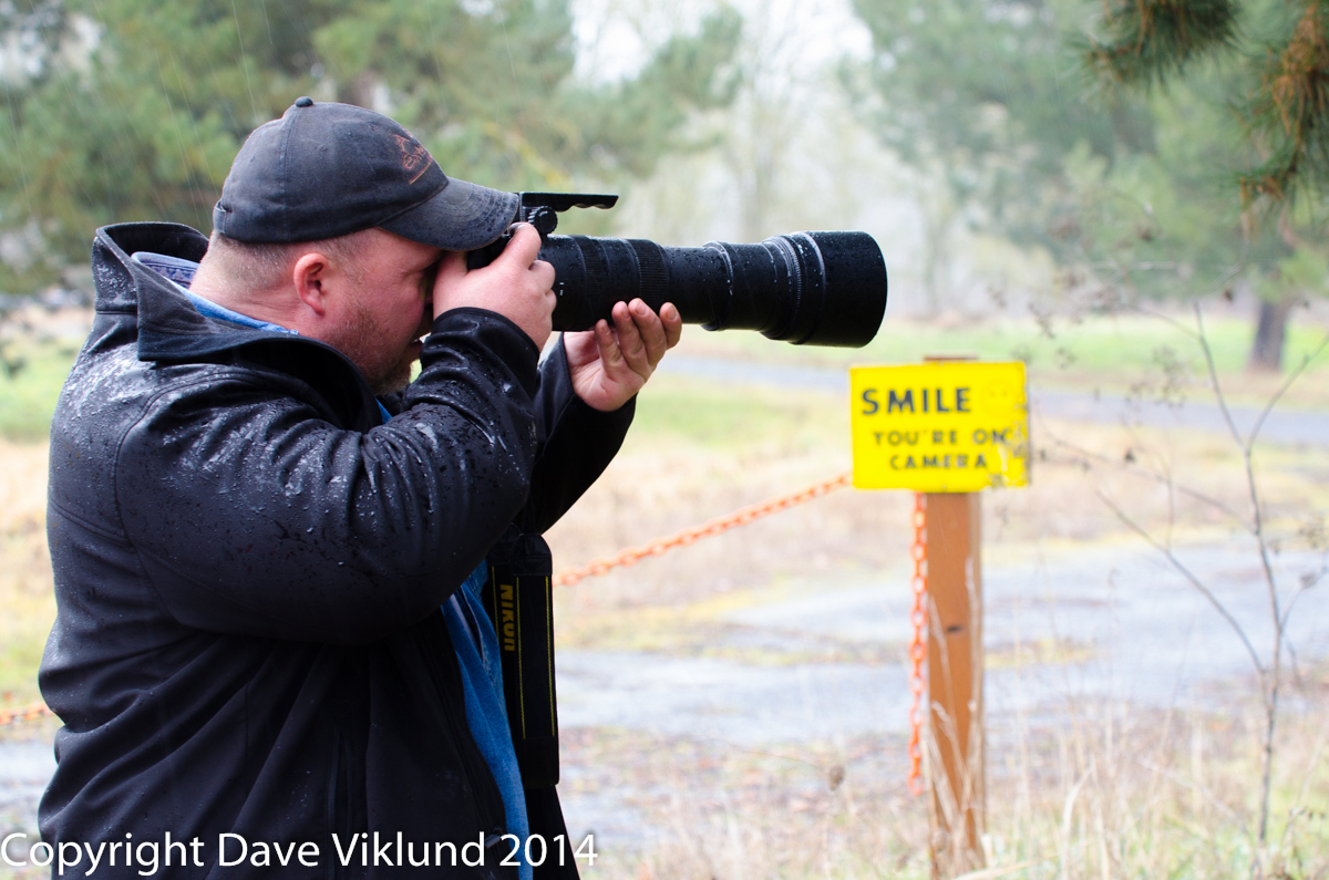 Photographer with a sign in the background that says smile your are on camera