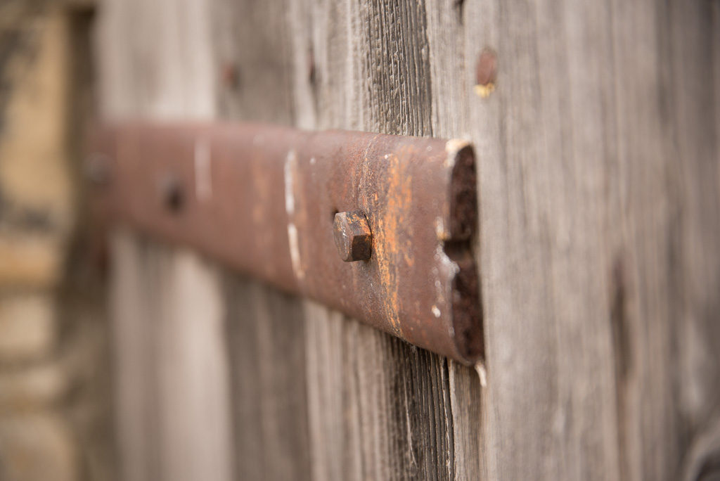Rusted hinges on old wooden door